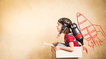 Child sitting in a cardboard box with leather helmet and a selfmade rocket (made with an old oil bottle) on its back