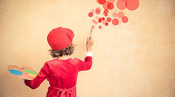 Child with a red french hat, paiting red circles on the wall